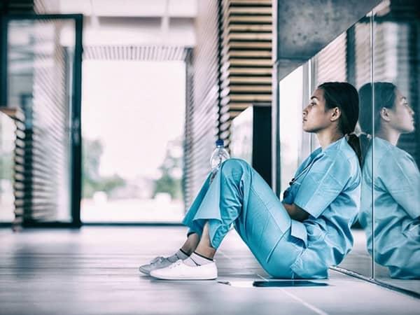 infermiera stressata seduta a terra